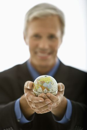 Selective focus of Caucasian middle aged businessman smiling and holding globe towards viewer. photo