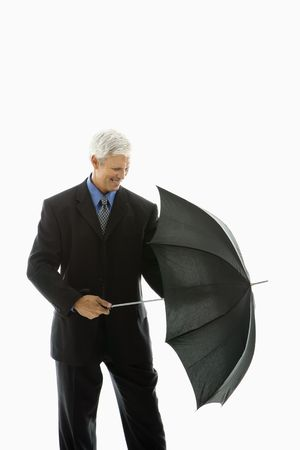 Caucasian middle aged businessman closing umbrella. photo