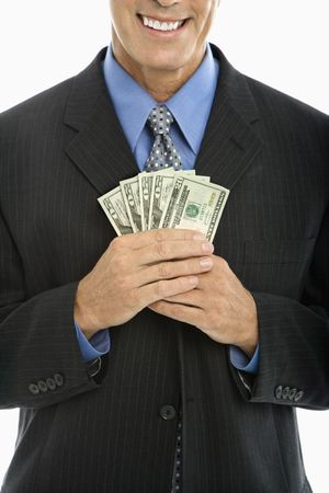 corporate greed: Caucasian middle aged businessman holding fist full of cash.