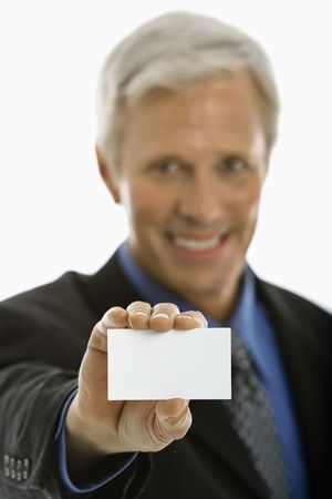 Caucasian middle aged man holding business card and smiling at viewer. photo