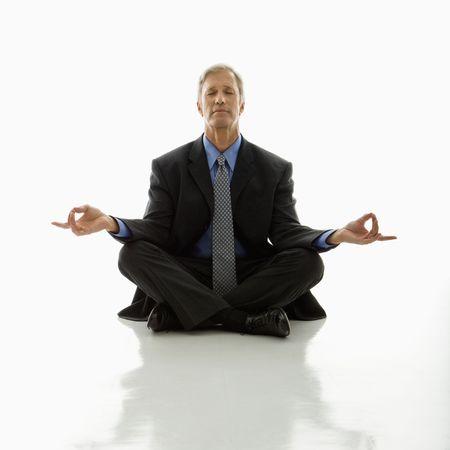 Caucasian middle aged businessman meditating in yoga lotus pose on floor. photo