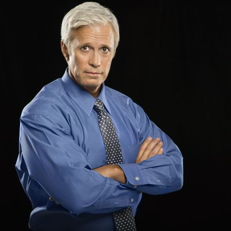 Caucasian middle aged businessman looking at viewer with arms crossed. photo