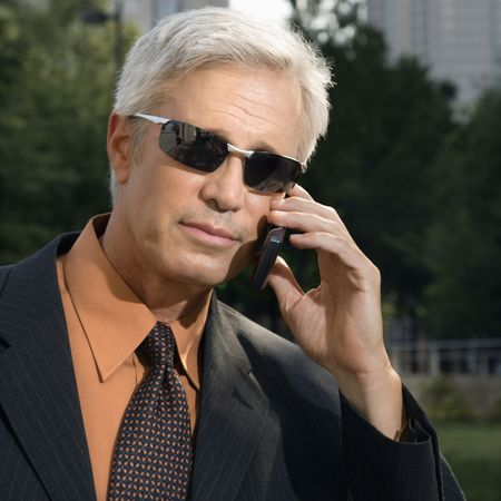 Caucasian middle aged businessman in sunglasses talking outdoors on cell phone. photo