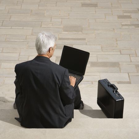 Caucasian businessman on steps outdoors with laptop and briefcase. photo