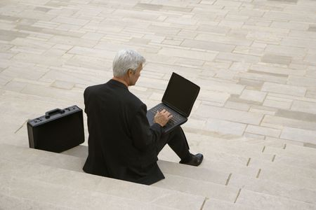 and the horizontal man: Back view of Caucasian middle aged businessman typing on laptop with briefcase sitting on steps outdoors. Stock Photo