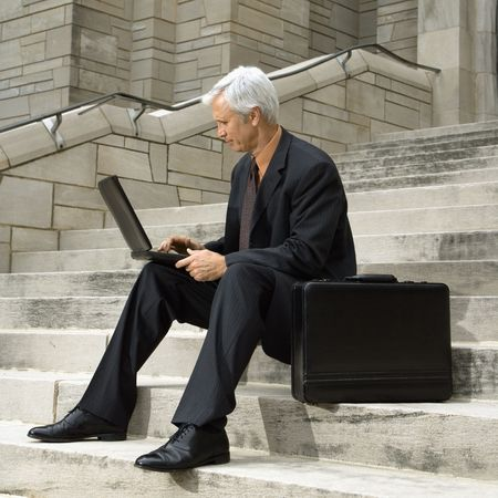 Caucasian middle aged businessman sitting on steps outdoors with laptop and briefcase. photo