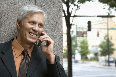 Caucasian middle aged businessman talking on mobile phone. photo