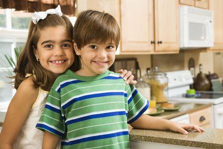 hispanic children: Hispanic children in kitchen smiling at viewer.