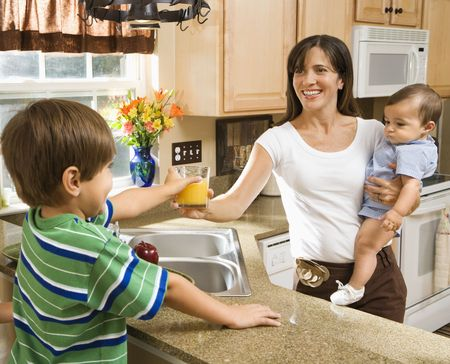 Hispanic mother and children in kitchen with juice.  photo