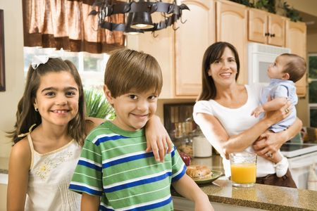 hispanic mother: Hispanic mother and children smiling at viewer in kitchen.