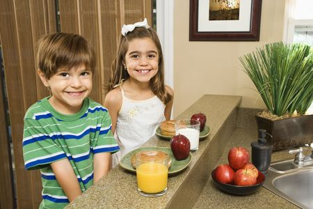 Young Hispanic brother and sister sitting at kitchen bar with healthy breakfast smiling at viewer. Stock Photo - 2555975