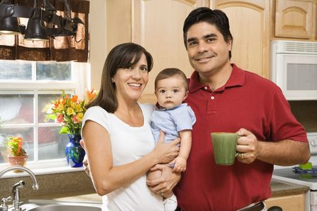 Hispanic family portrait in home kitchen with baby.  photo