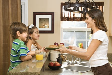 Hispanic mother handing healthy breakfast to young children in home kitchen. Stock Photo - 2555942