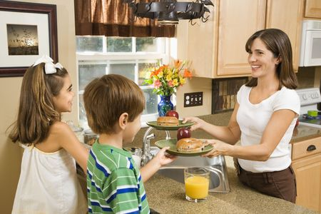 hispanic mother: Hispanic mother giving healthy breakfast to young children in home kitchen.