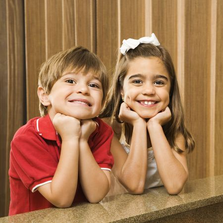 hispanic children: Hispanic children with their head on hands smiling at viewer.