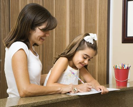 hispanic mother: Hispanic mother helping daughter with homework. Stock Photo