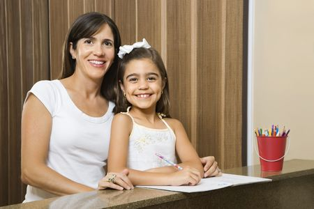 Hispanic mother and daughter portrait with homework. Stock Photo - 2555845