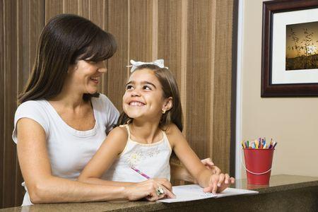 hispanic mother: Hispanic mother helping daughter making eye contact and working on homework.
