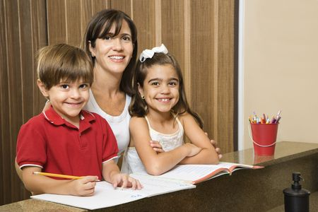 hispanic mother: Hispanic mother and children smiling at viewer with homework. Stock Photo