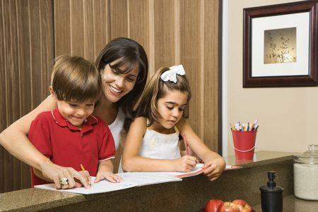 Hispanic mother helping children with homework. photo