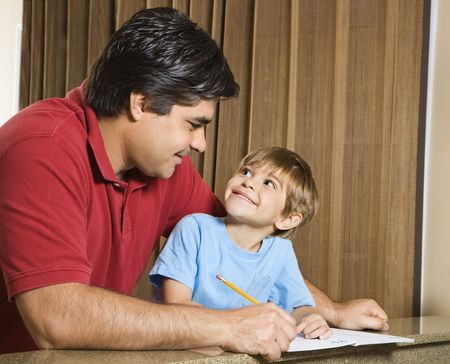 Hispanic father and   son doing homework and making eye contact. Stock Photo - 2555977