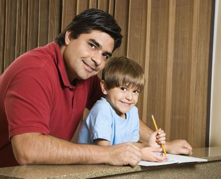 Hispanic father and son smiling at viewer with homework. Stock Photo - 2555982