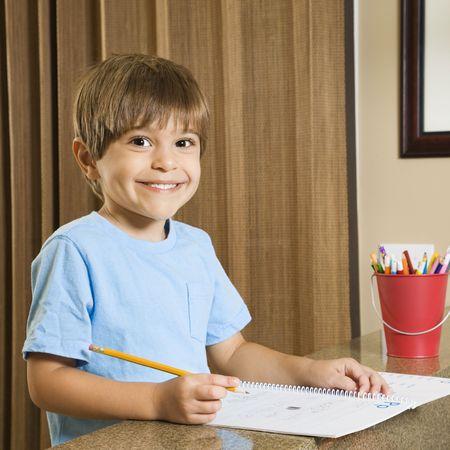 hispanic boy: Hispanic ni�o sonriente en espectador y hacer la tarea.  Foto de archivo
