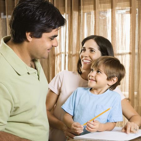Hispanic parents making eye contact with son doing homework. Stock Photo - 2555936