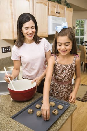 hispanic mother: Hispanic mother and daughter in kitchen making cookies.
