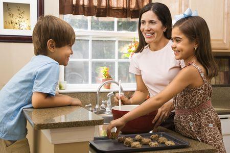 hispanic mother: Hispanic mother and children in kitchen making cookies.