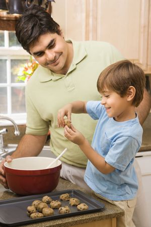 Hispanic father and son in kitchen making cookies. photo