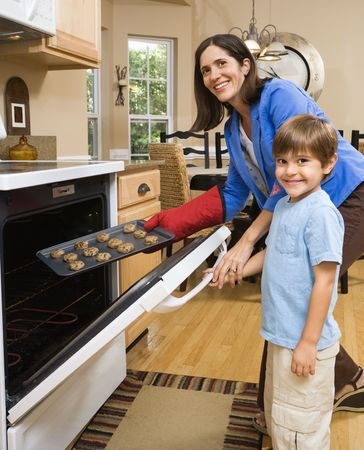 Hispanic mother and son putting cookies into oven and smiling at viewer. photo
