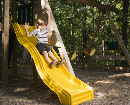 above head: Hispanic boy sliding down outdoor slide with arms raised above head.
