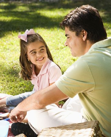 Hispanic father and daughter outsdoors smiling at each and relaxing on grass. photo