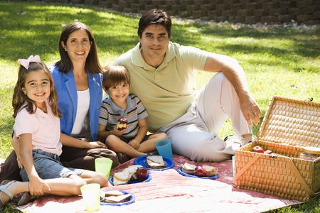 Hispanic family picnicking in the park and smiling at viewer. photo