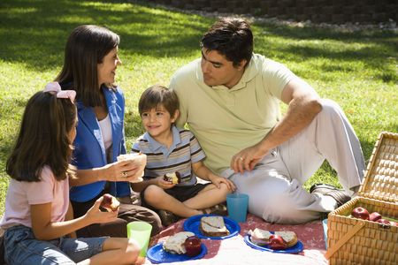 hispanic boy: Familia hispana de picnic en el parque. Foto de archivo