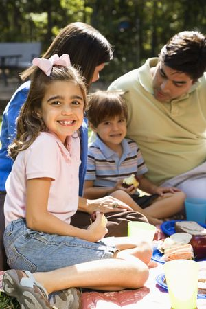 Hispanic girl smiling at viewer with family picnicking in the park. Stock Photo - 2555907