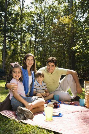 family eating: Familia hispana picnic en el parque y sonriente en el visor.