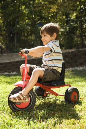 Side view of Hispanic boy riding red tricycle in grass.