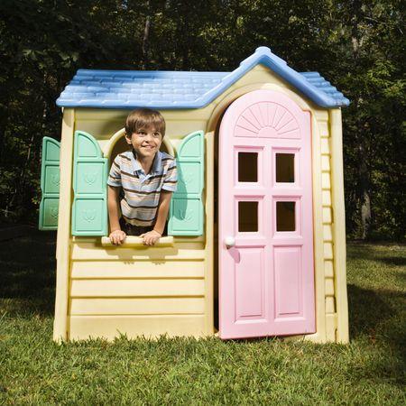 hispanic boy: Muchacho hisp�nico en la ventana del playhouse al aire libre que sonr�e en el espectador.
