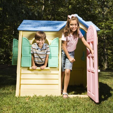 Hispanic boy and girl in outdoor playhouse smiling at viewer. photo