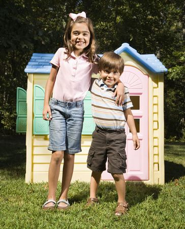 playhouse: Hispanic boy and girl in front of outdoor playhouse smiling at viewer.