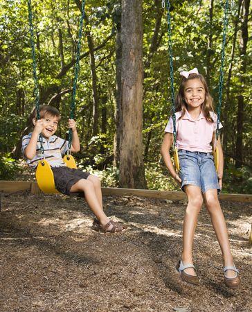 Hispanic boy and girl on swing set smiling at viewer. photo