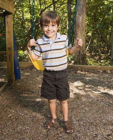 Hispanic boy standing by swing set smiling at viewer. photo