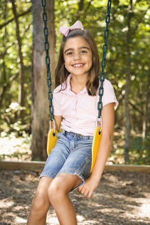 Hispanic girl sitting on swing smiling at viewer. photo