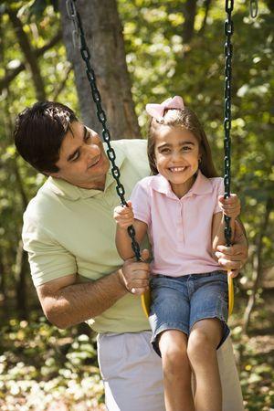 Hispanic father pushing daughter on swing. photo