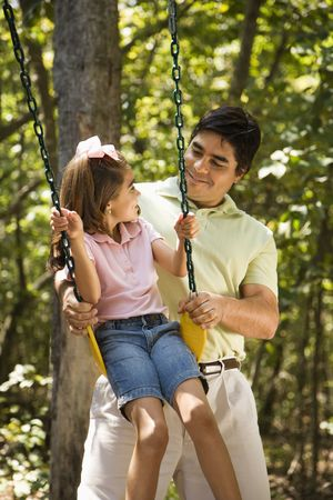 Hispanic father pushing daughter on swing and making eye contact. photo
