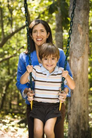 Hispanic mother pushing son on swing and smiling at viewer. photo