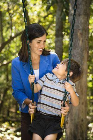Hispanic mother pushing son on swing and making eye contact. photo