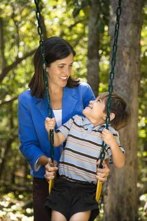Hispanic mother pushing son on swing and making eye contact. Stock Photo - 2555869